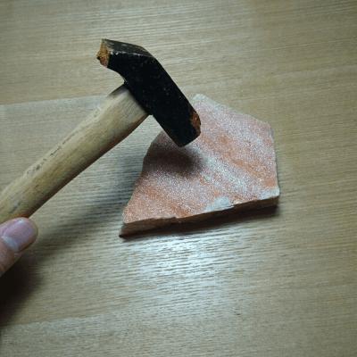 石をかなづちで割る
